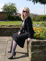 Sexy secretary Milf Jenny takes her lunch break outdoors wearing her nice suit, sunglasses, sexy nylons and tall shiny black stilettos